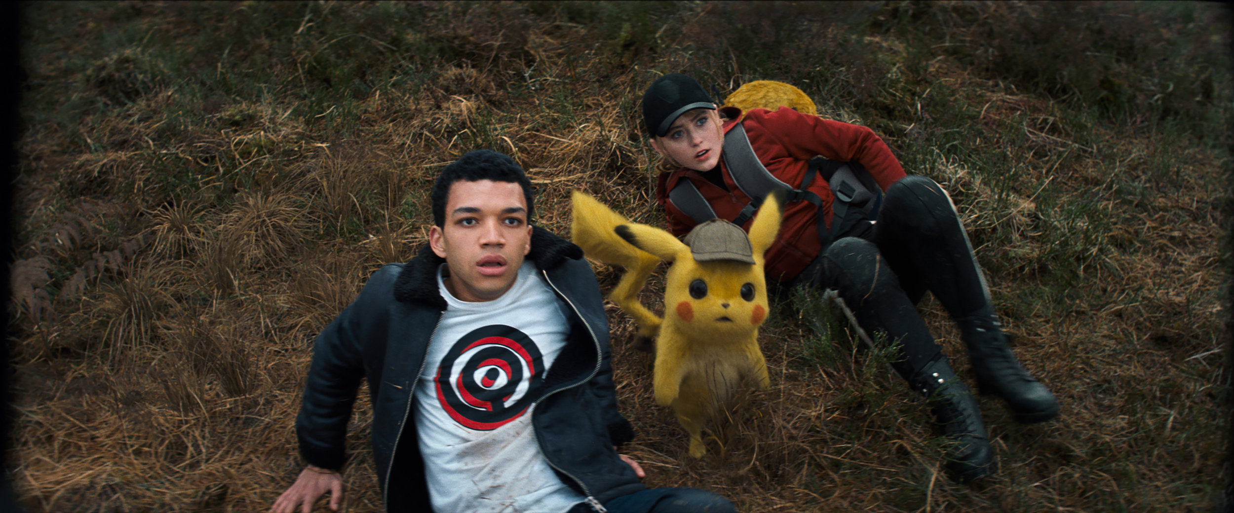 "Tim Goodman (Justice Smith, left) and Lucy Stevens (Kathryn Howard, right) team up with a sleuthing Pikachu (voiced by Ryan Reynolds) when things go awry, in the action-adventure ""Pokémon Detective Pikachu."" (Photo courtesy of Warner Bros. Pictures.)"