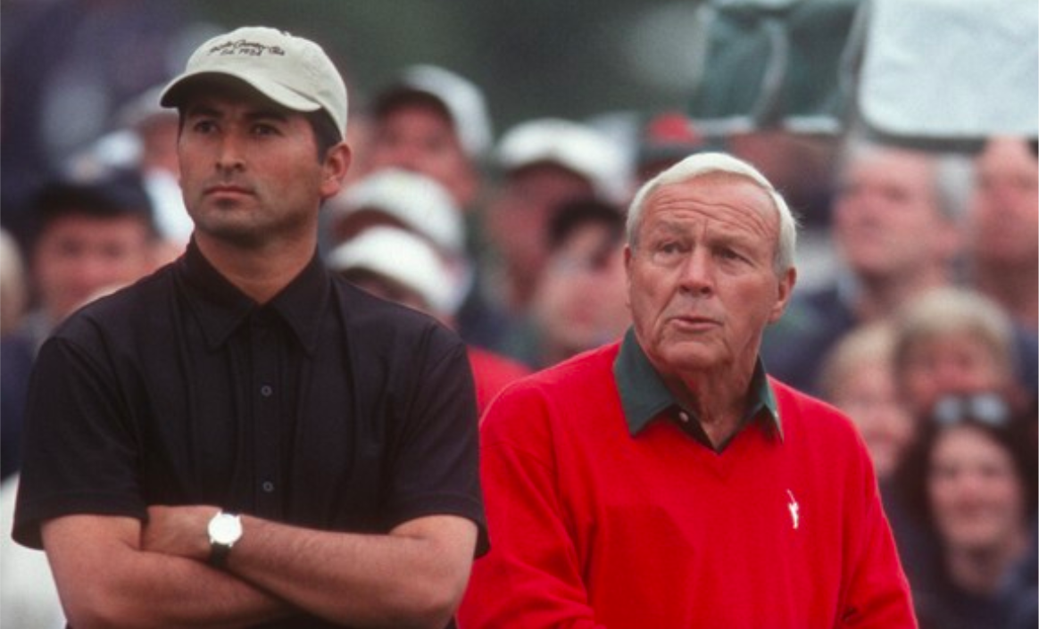 """Greg Puga, a golfer and caddie from east Los Angeles, stands alongside the legendary Arnold Palmer at The Masters in 2001 — in which Puga qualified — in a moment seen in the documentary """"Loopers: The Caddie's Long Walk."""" (Photo courtesy Jason Baffa Films.)"""