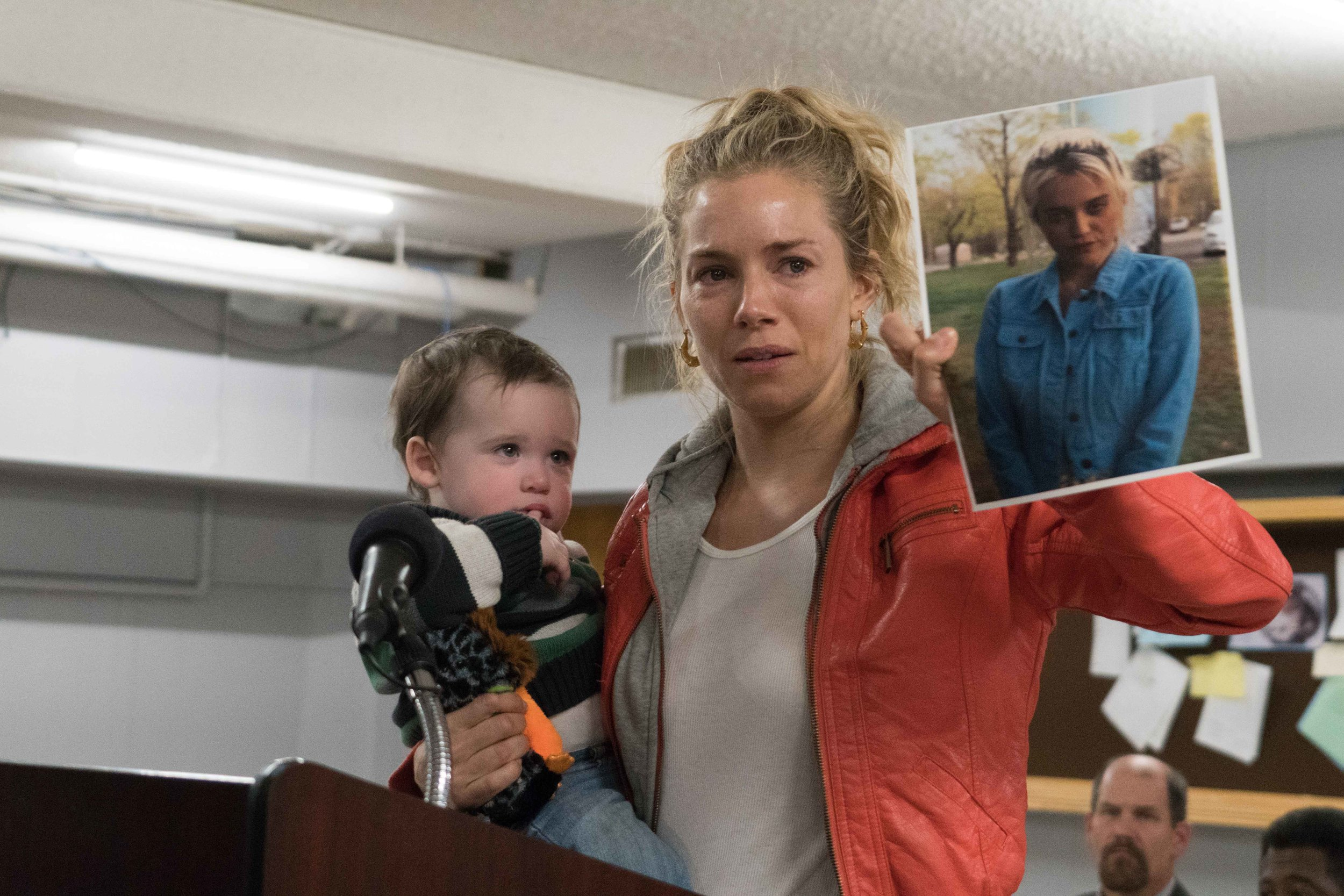"Debra Callahan (Sienna Miller) holds her grandson in one hand and a photo of her missing daughter, Bridget (Sky Ferreira) in the other, in a scene from the drama ""American Woman."" (Photo by Seacia Pavao, courtesy of Roadside Attractions.)"
