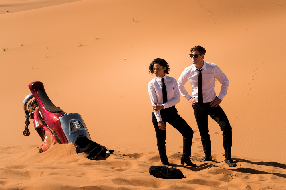 "Agents M (Tessa Thompson, left) and H (Chris Hemsworth) adjust to being stranded in the desert, in a moment from the action comedy ""Men in Black: International."" (Photo by Giles Keyte, courtesy of Columbia Pictures.)"
