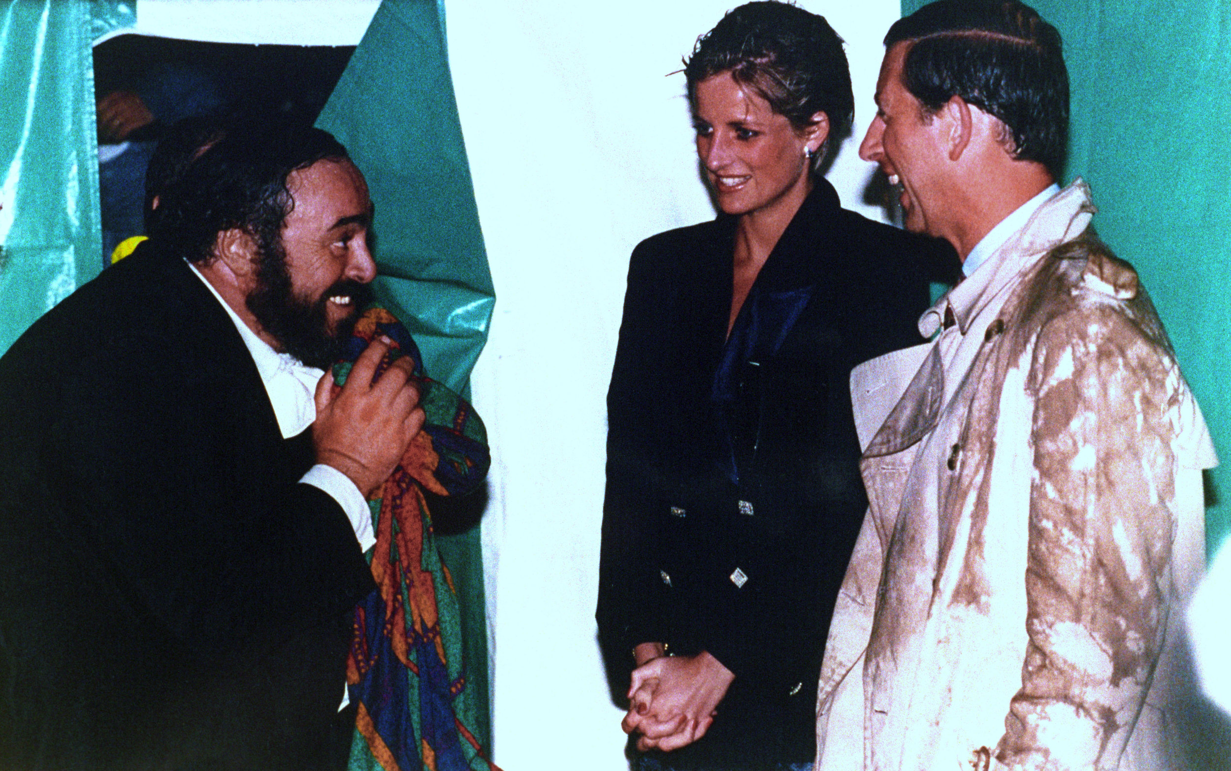 """Tenor Luciano Pavaroti, left, meets a rain-drenched Princess Diana and Prince Charles after an outdoor concert in London, in an image seen in the documentary """"Pavarotti."""" (Photo courtesy of PA Images / Alamy Stock Photo / CBS Films.)"""