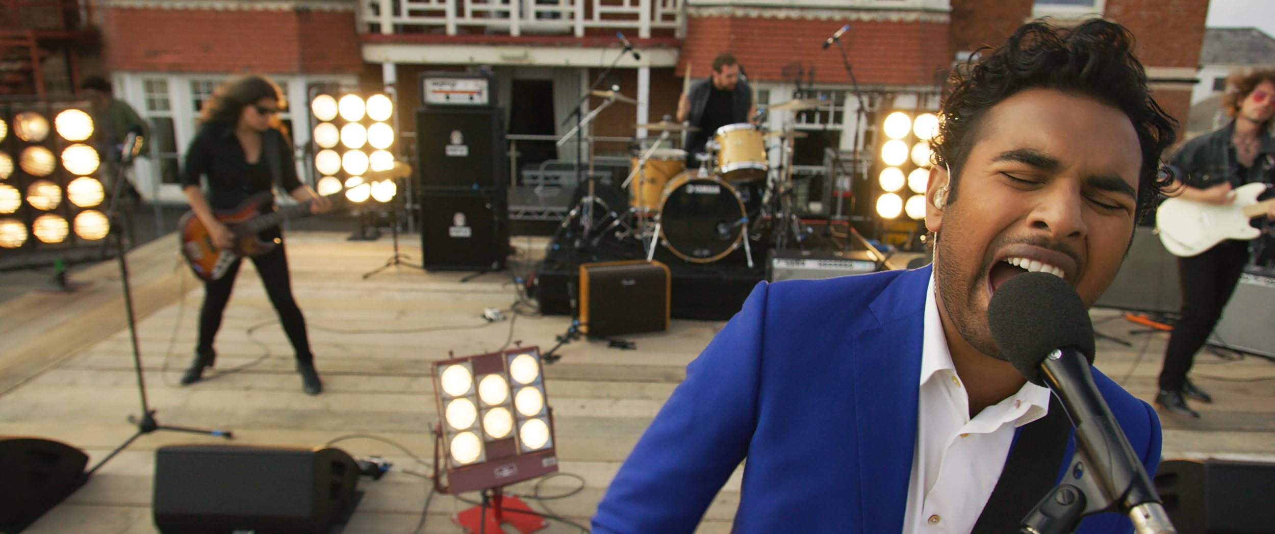 """Jack Malik (Himesh Patel, right) performs a rooftop concert of Beatles songs, in a scene from the romantic comedy """"Yesterday."""" (Photo courtesy of Universal Pictures.)"""