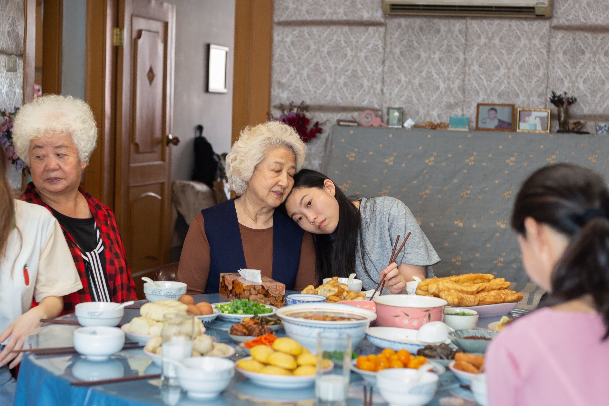 """Billi (Awkwafina, right), a Chinese-American academic, takes comfort from her grandmother, Nai Nai (Shuzhen Zhou), during a family gathering in China, in Lulu Wang's comedy-drama """"The Farewell."""" (Photo courtesy of A24 Films.)"""