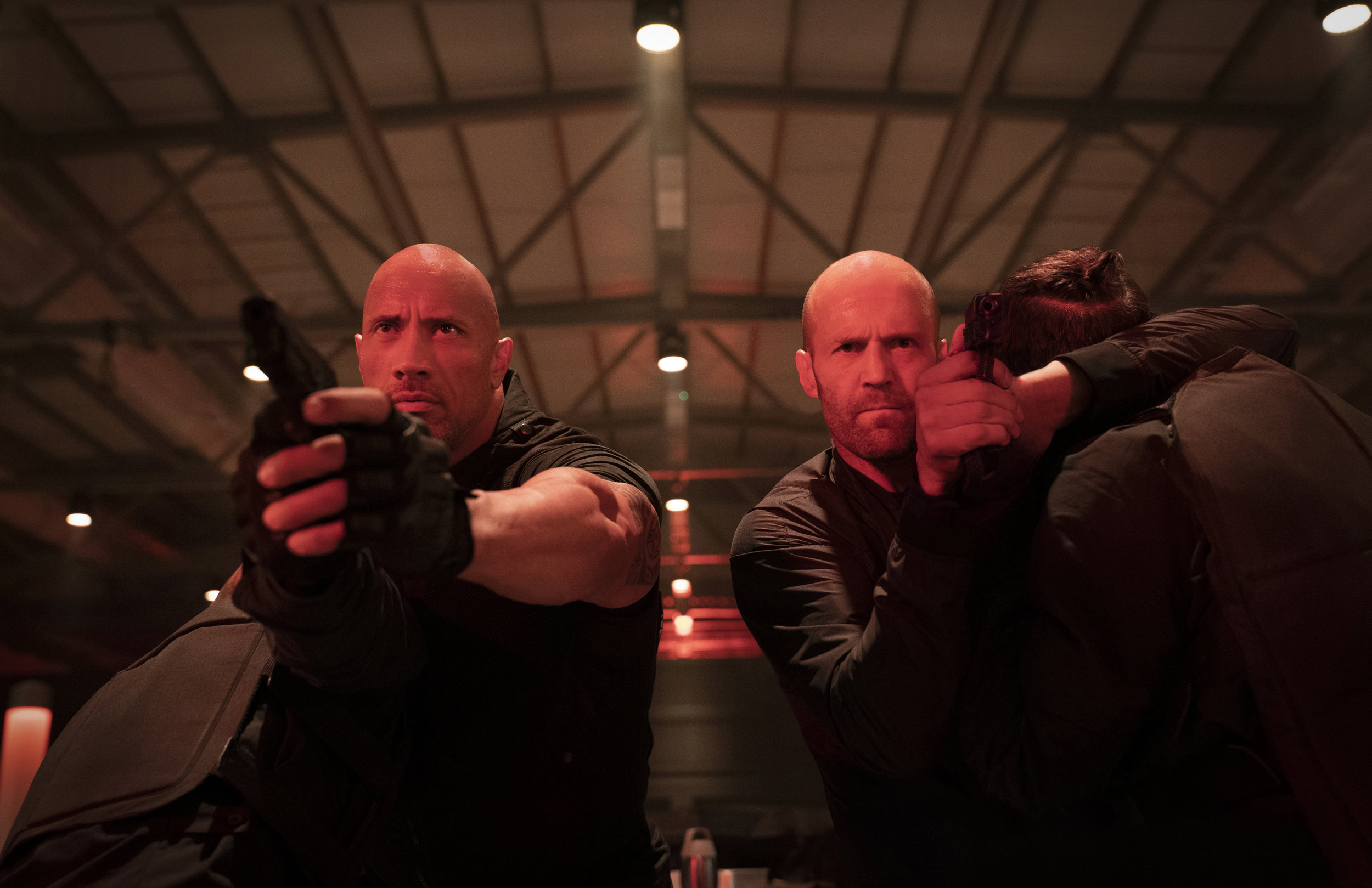 """Luke Hobbs (Dwayne Johnson, left) and Deckard Shaw (Jason Statham) face a small army of gunmen in a scene from """"Fast & Furious Presents: Hobbs & Shaw."""" (Photo by Daniel Smith, courtesy of Universal Pictures.)"""
