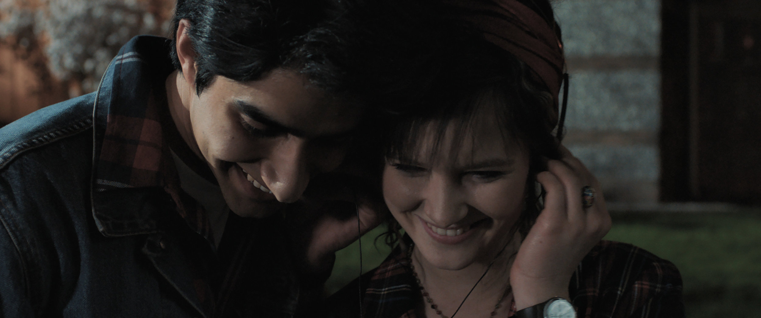 """Javed (Viviek Kalra, left) and Eliza (Nell Williams) share headphones to listen to Bruce Springsteen, in a moment from the coming-of-age story """"Blinded by the Light."""" (Photo courtesy of Warner Bros. Pictures.)"""