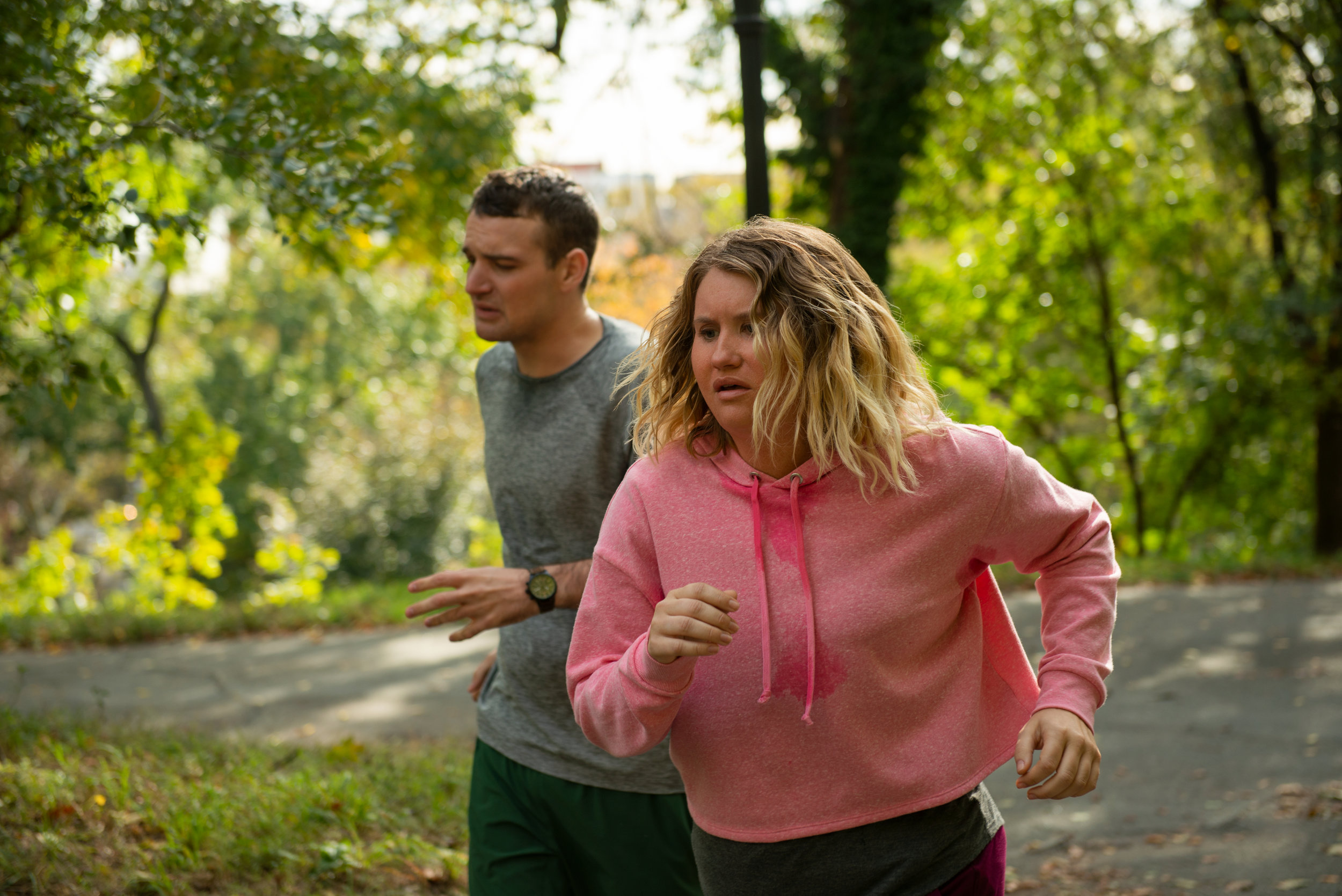 """Brittany (Jillian Bell, right) and her new running partner, Seth (Micah Stock), suffer through their first run, in a scene from the comedy """"Brittany Runs a Marathon."""" (Photo by Anna Kooris, courtesy of Amazon Studios.)"""
