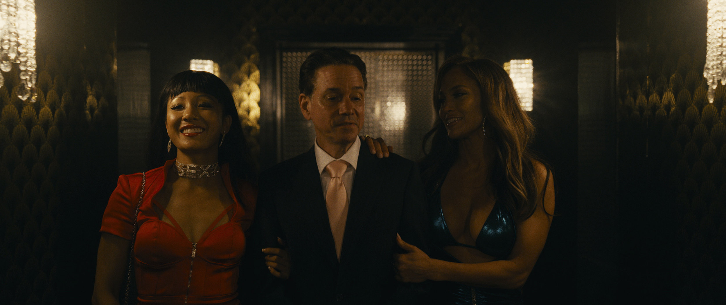 """Strippers-turned-con artists Destiny (Constance Wu, left) and Ramona (Jennifer Lopez, right) work their charms on a Wall Street executive (Frank Whaley) in the true-crime drama """"Hustlers."""" (Photo courtesy of STX Films.)"""