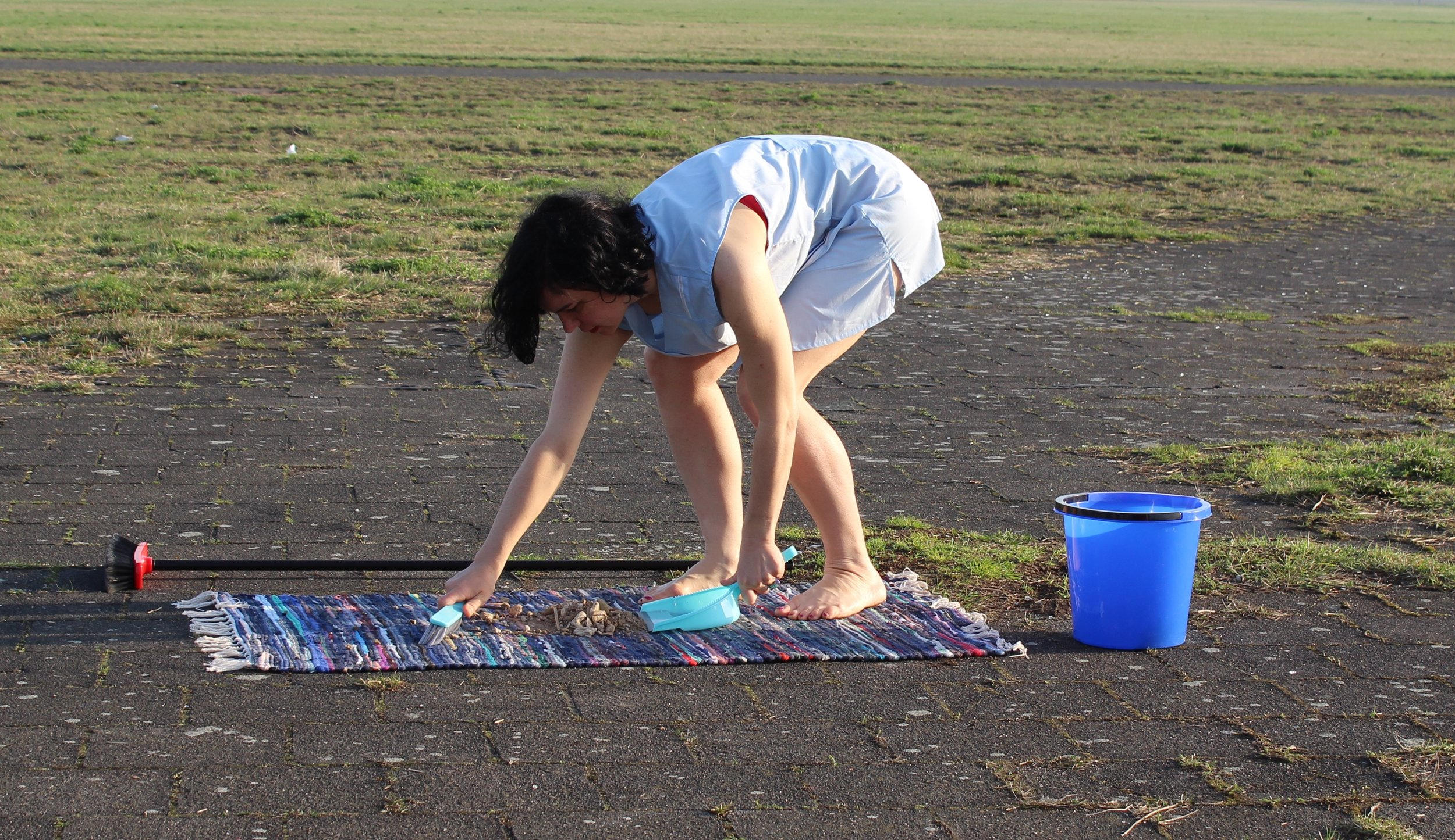 """Artist Michelle Standley performs her work """"4.5 Hours,"""" in which she continuously sweeps a rug to highlight issues of domestic labor, at Berlin's decommissioned Tempelhof Airport on April 1, 2017. Standley will repeat the performance on Sunday, Oct. 6, at Salt Lake City's Temple Square. (Photo by Michelle Standley, courtesy of the artist.)"""