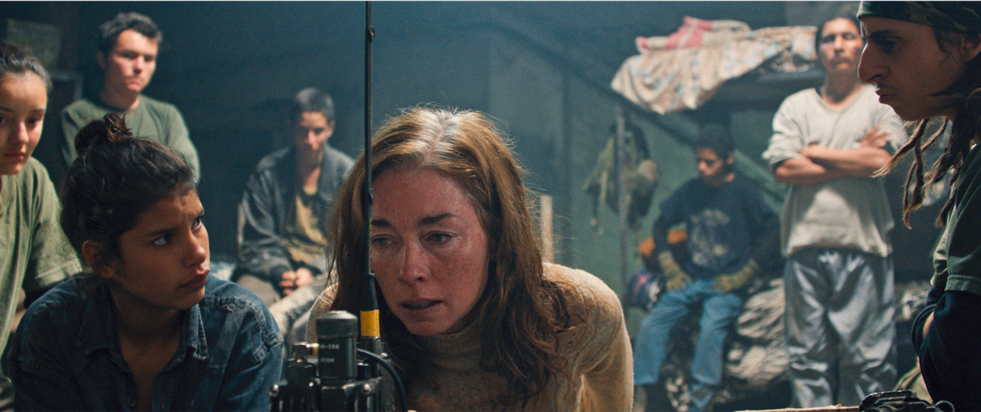 """Sara Watson (Julianne Nicholson, center) answers questions via radio to satisfy her captors, including the teen soldiers holding her in a South American country, in the drama """"Monos."""" (Photo courtesy of Neon.)"""