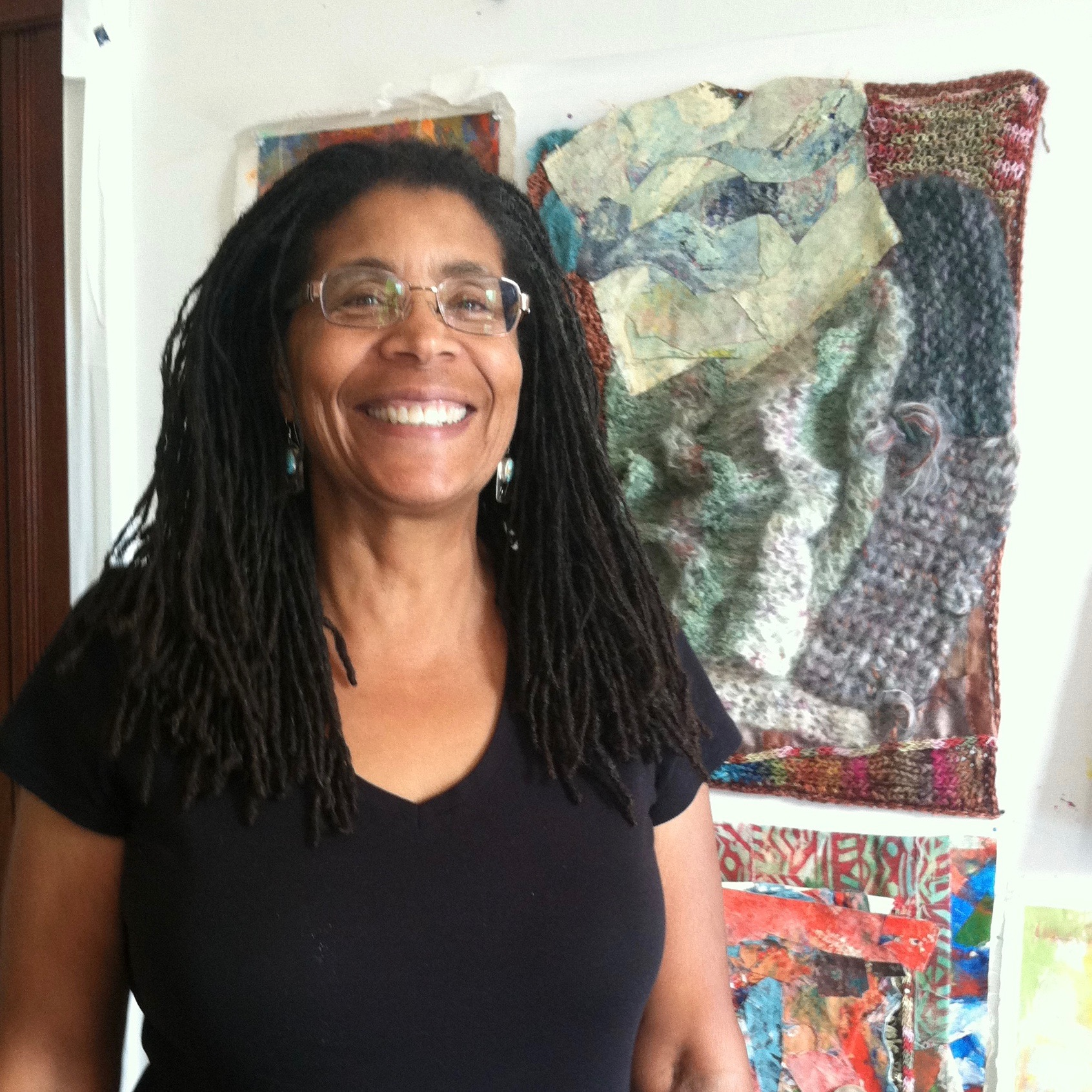 woman smiles in front of her oil painting