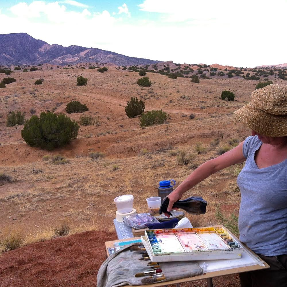 woman works outdoors on a painting with spray bottle in hand