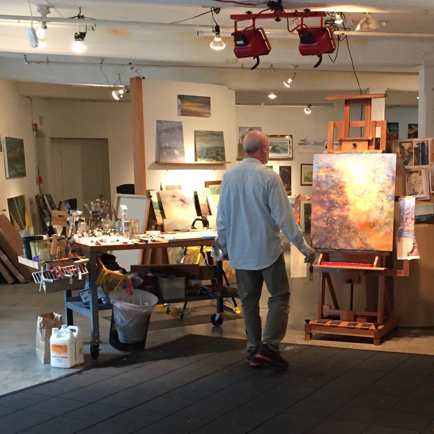 man walking through a studio full of artwork
