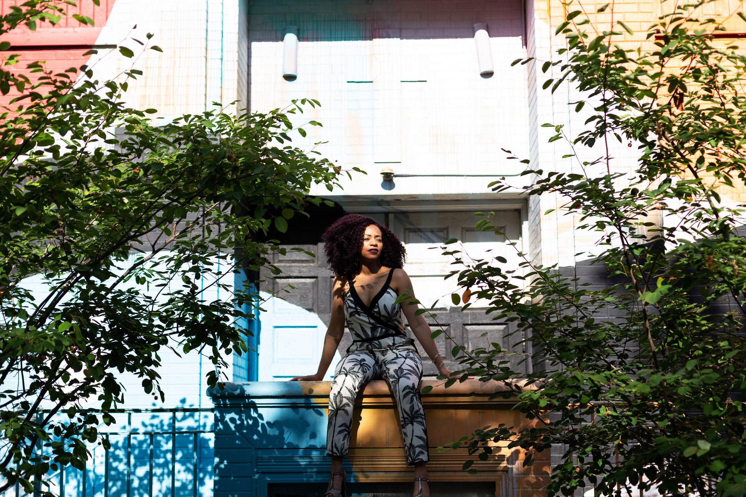 Black Woman Sitting On Ledge