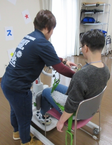 Training programs demonstrate how to use a standing machine to help lift a patient from bed to standing position without straining the caregiver's back.