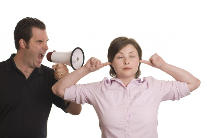 man yelling megaphone woman fingers in ears.jpg