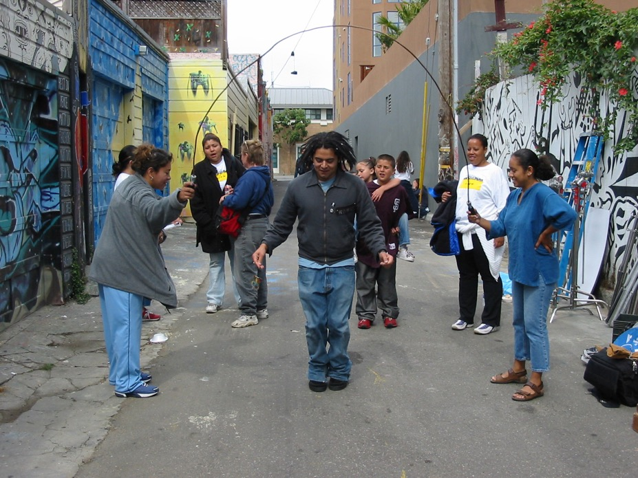 Figure 8: Collaborating filmmaker and casting director Harjant Gill goofing-off/skipping-rope with crew members between shots on the set of Mission Movie in Clarion Alley.
