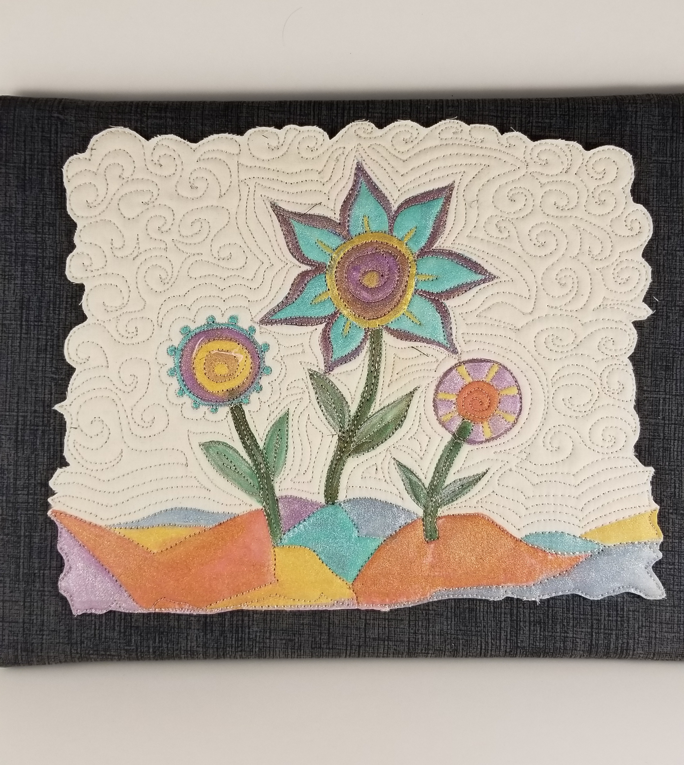 Paint, free motion quilting, and thread sketching on fabric. -