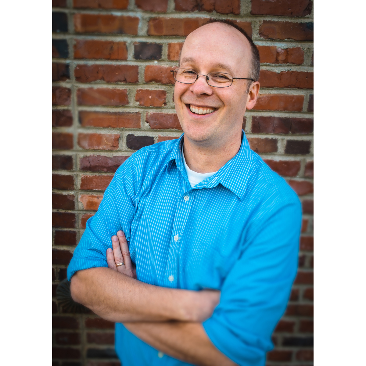 environmental portrait of professional man with glasses in blue shirt against brick wall