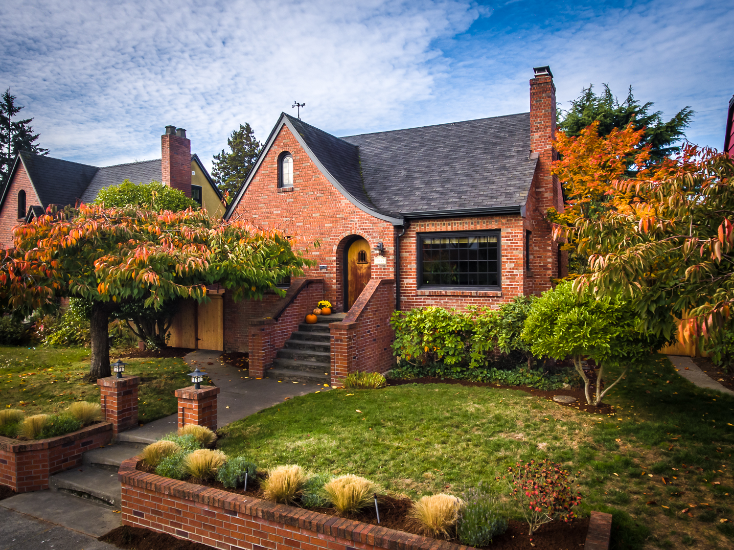 Drone photo of brick house exterior with blue sky in Autumn