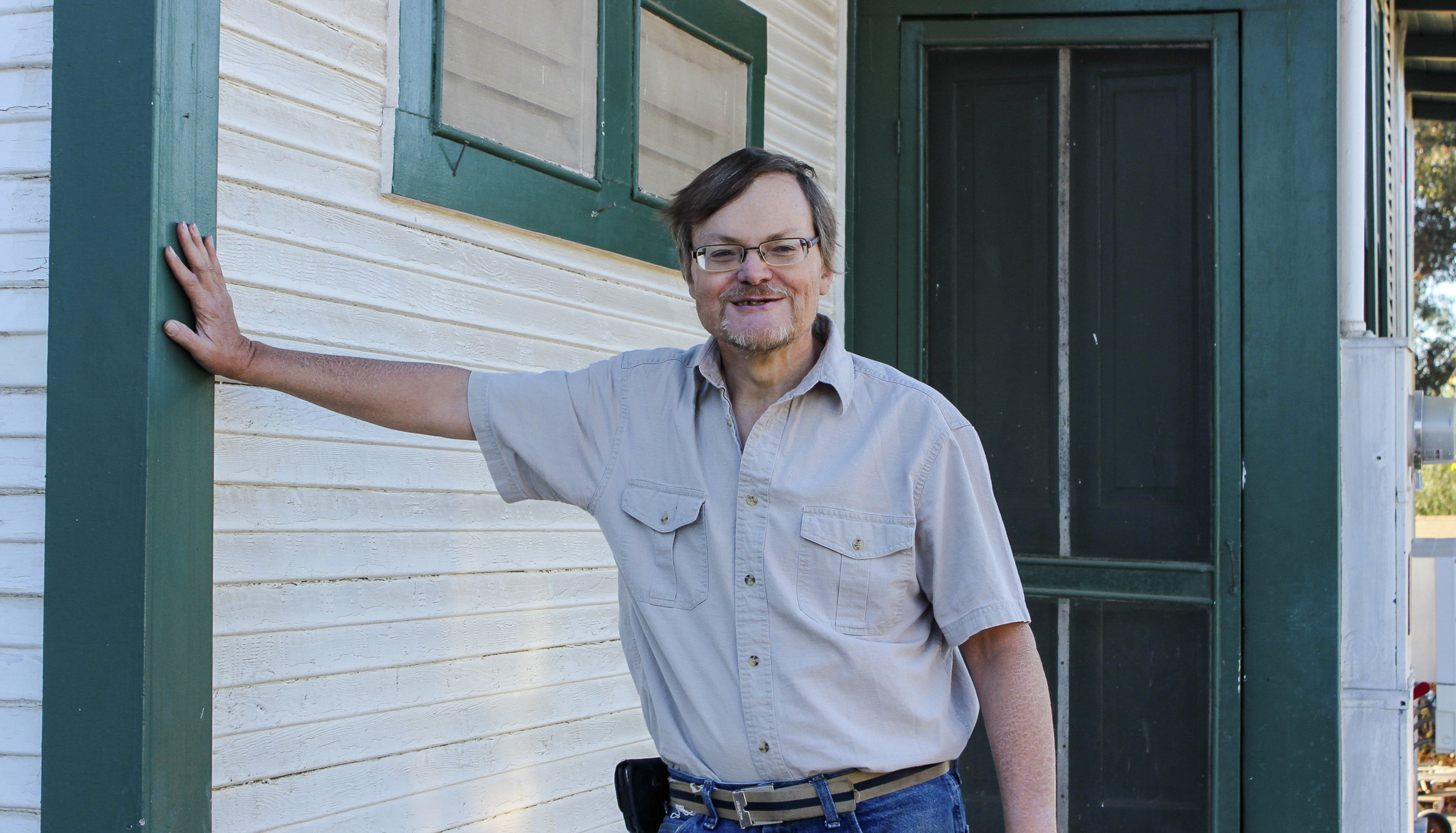 Former Interfaith shelter participant Brian poses in front of his new home.