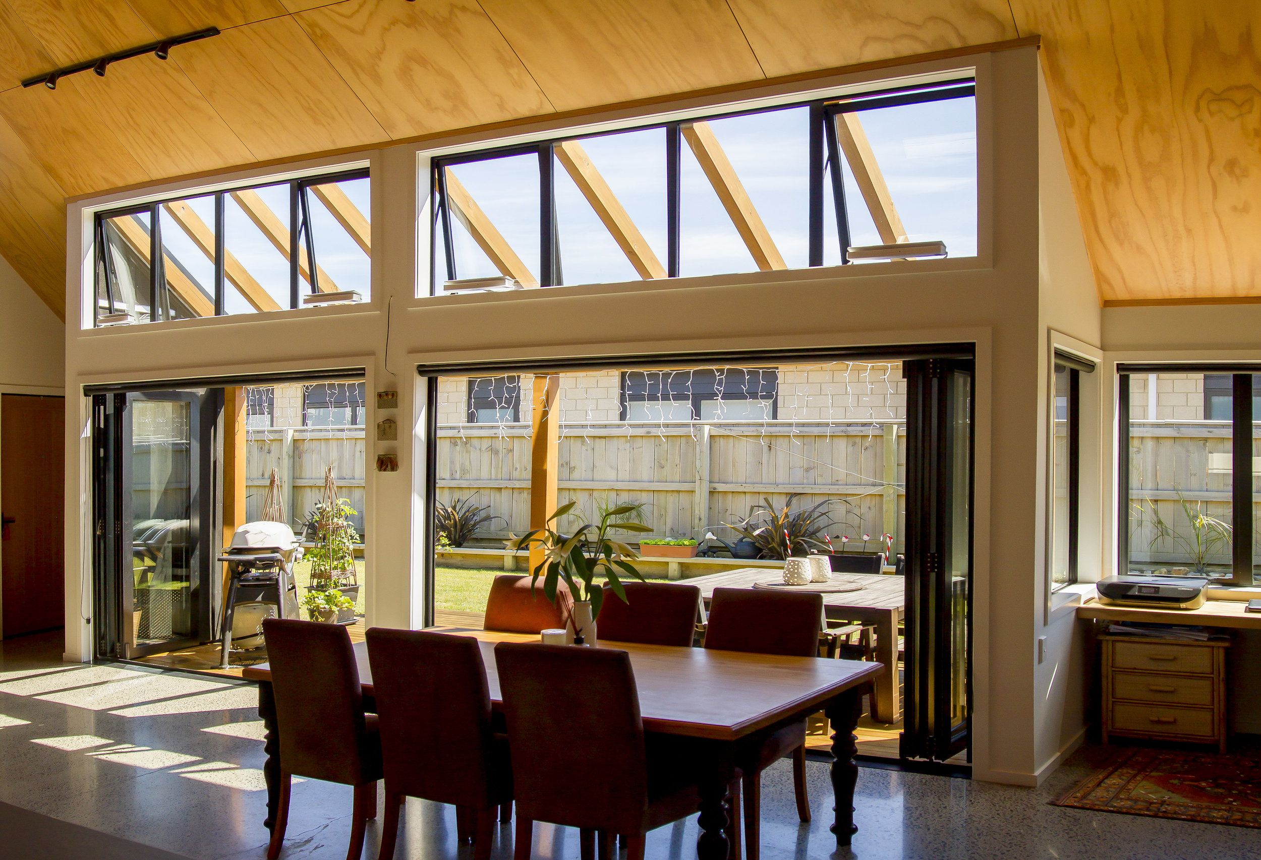 High Windows  - The high windows reveal the outside pergola that continues the roof line, while also letting more light into the living area.