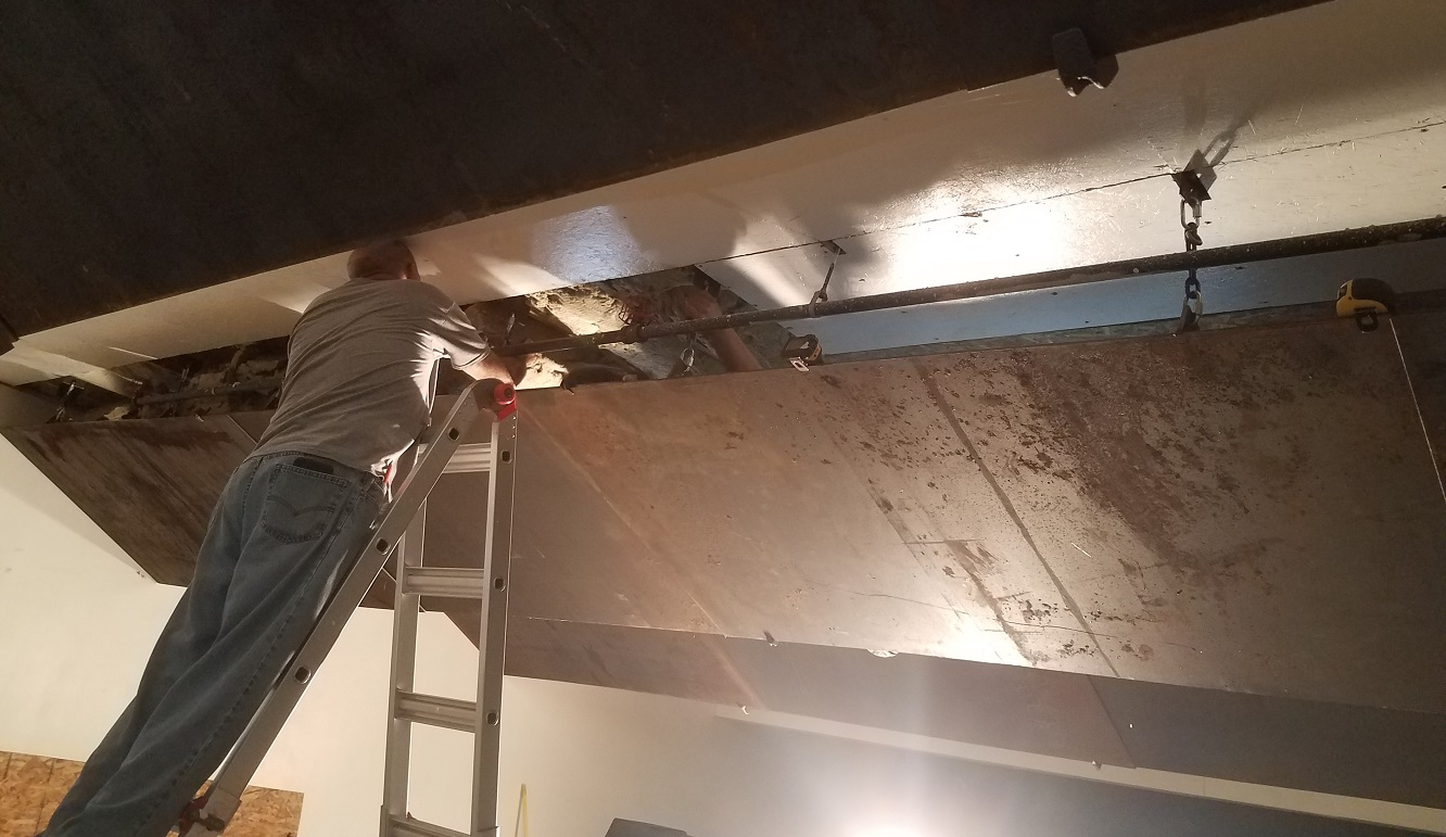 This row of baffles was installed adjacent to one of the transverse beams leaving no room for external ceiling repair. The panels were removed for the installation of the steel hangers