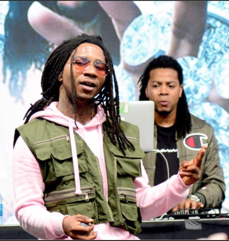 Above is a photo of Lil B, in pink, with Keyboard Kid DJing behind him.