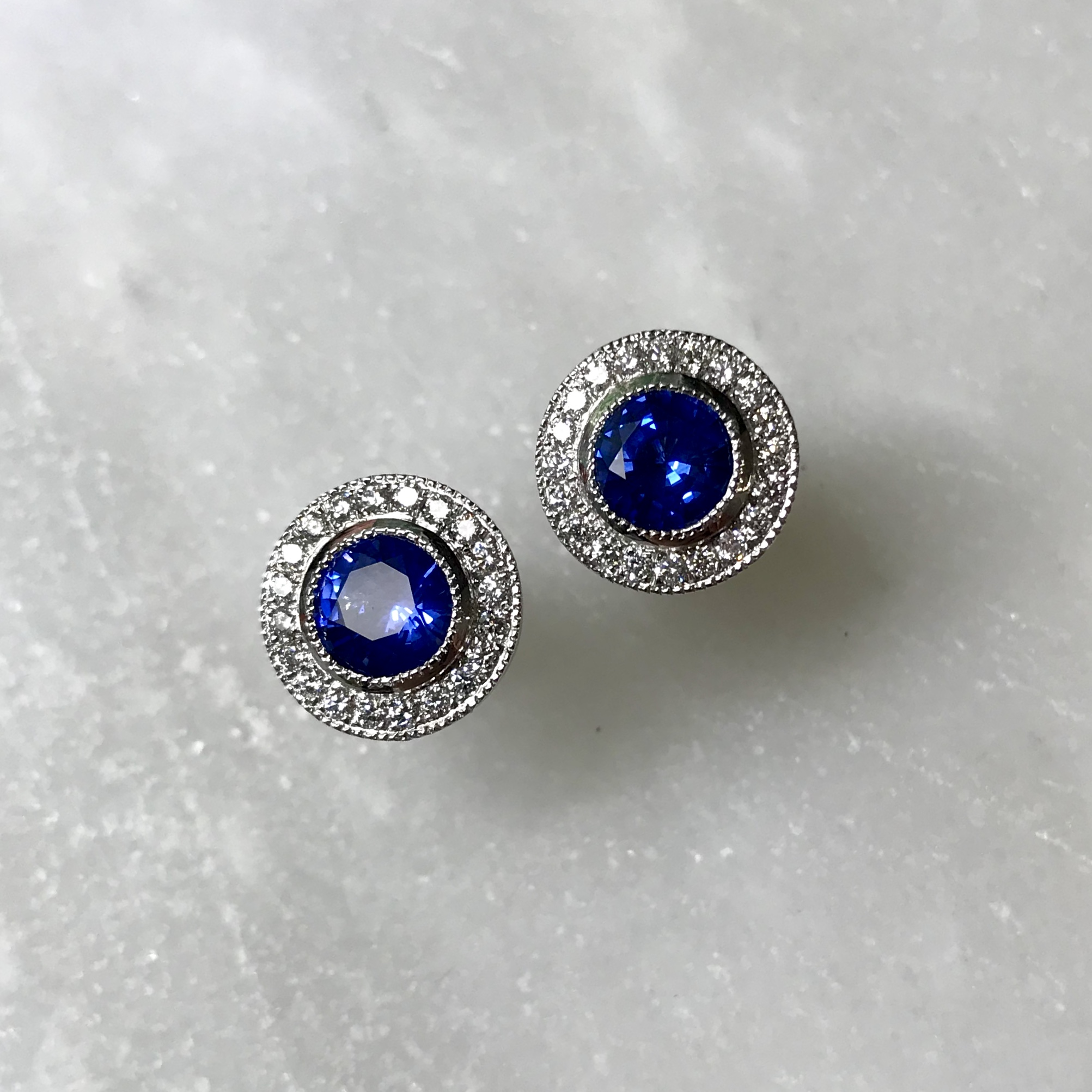 Made to order - Platinum Sapphire and Diamond Halo earrings. Designed to match a previous engagement ring commission.