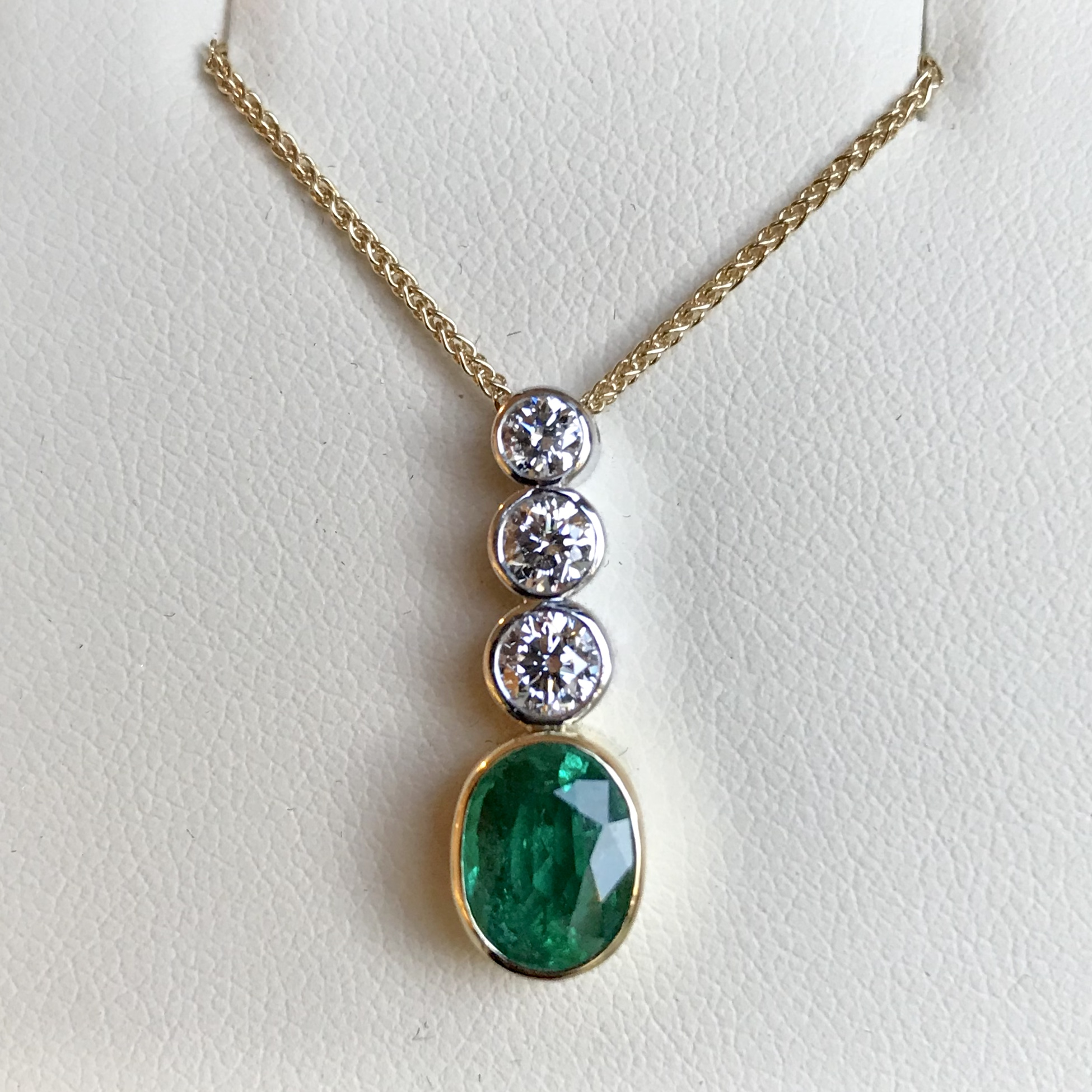 Made to order - 18ct yellow gold graduated Diamond and oval Emerald pendant.