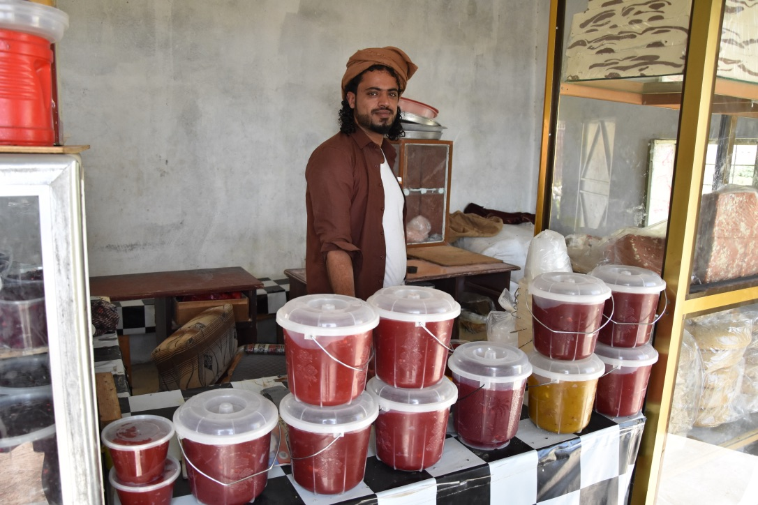 A Yemeni man stands in front of some traditional desserts