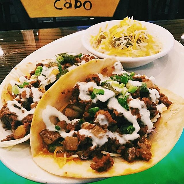 You already know what day it is 🌮 These chorizo tacos from @cabo_roanoke look like they would hit the spot. Grilled chorizo tacos sauteed with diced potatoes, onions, peppers on a bed of cabbage, tomato, and cheese topped with roasted garlic crema sauce 💯 #vafoodie 📷: @cabo_roanoke