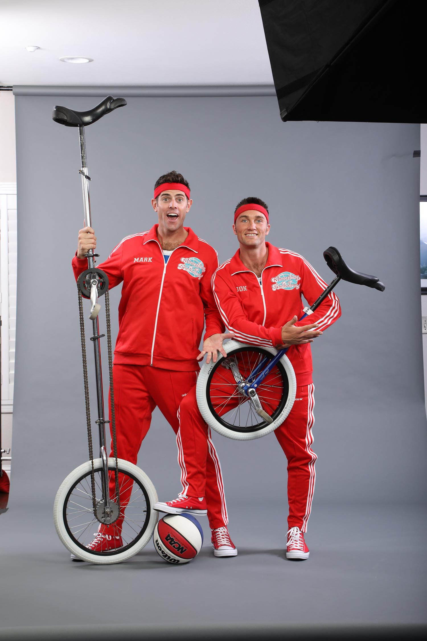 Jon and Mark in red jumpsuits with unicycles