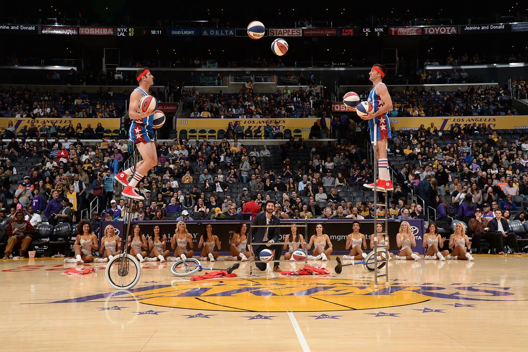 LA Lakers halftime show Jon and Mark on tall unicycles juggling basketballs