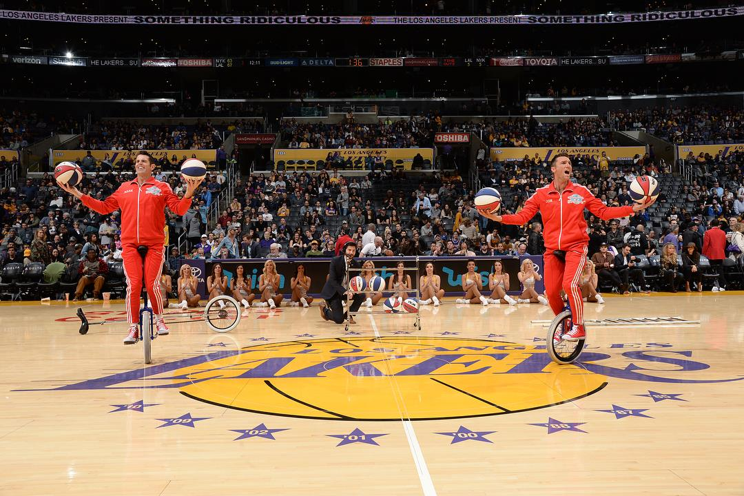 LA Lakers halftime show Jon and Mark on short unicycles juggling basketballs
