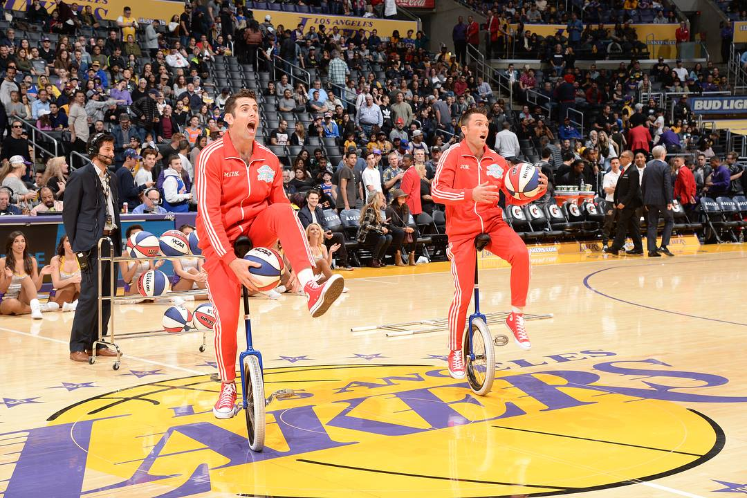 LA Lakers halftime show Jon and Mark on short unicycles playing with basketballs