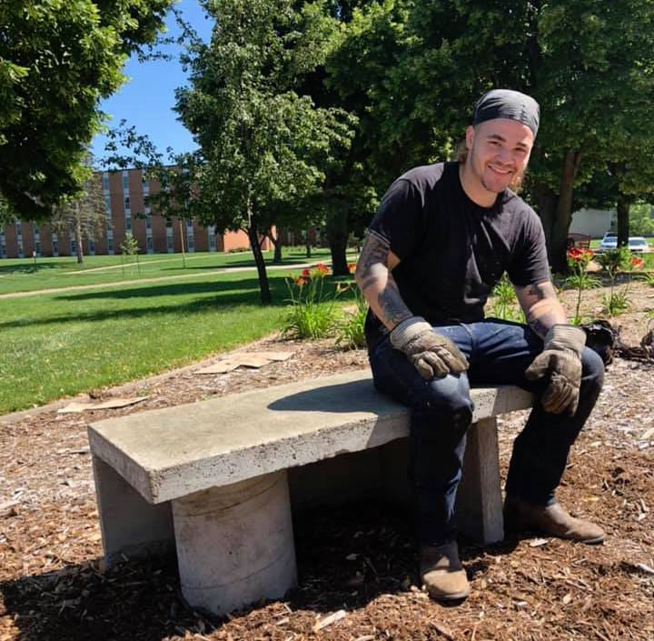 Levi Sternburg models the concrete form of his first bench, which will be covered in tiles painted by members of the Vermillion community during the workshop on Saturday, September 7.