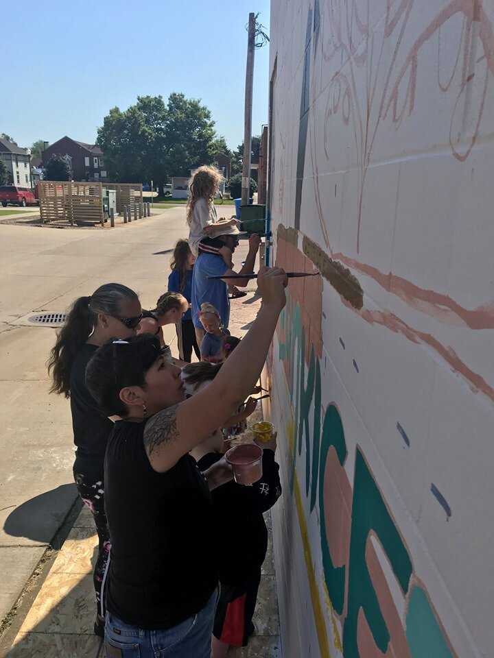 Vermillionaires make the stretch to reach higher parts of the design during the community paint day.