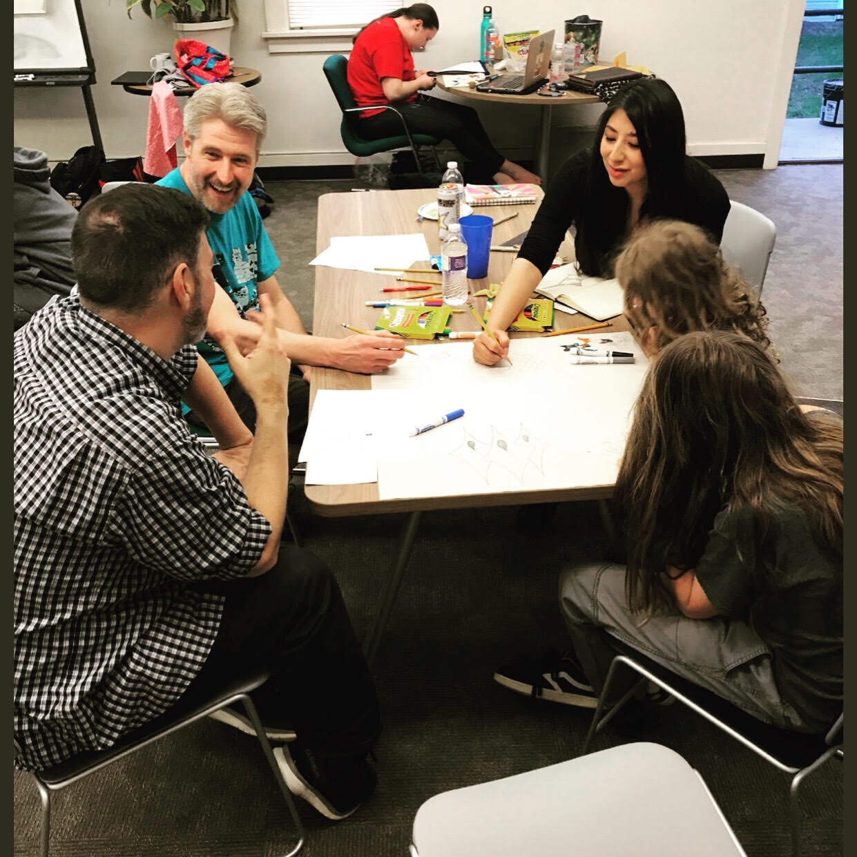 Community members and lead muralist Reyna Hernandez (center) brainstorm at the first design session, hosted by the Native American Cultural Center.