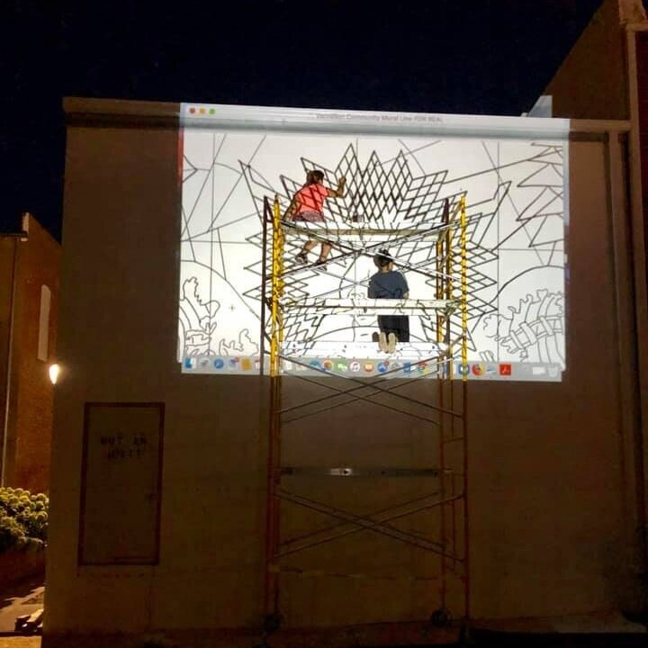Line art is projected onto the primed wall of the Coyote Twin at night for the artists to trace.