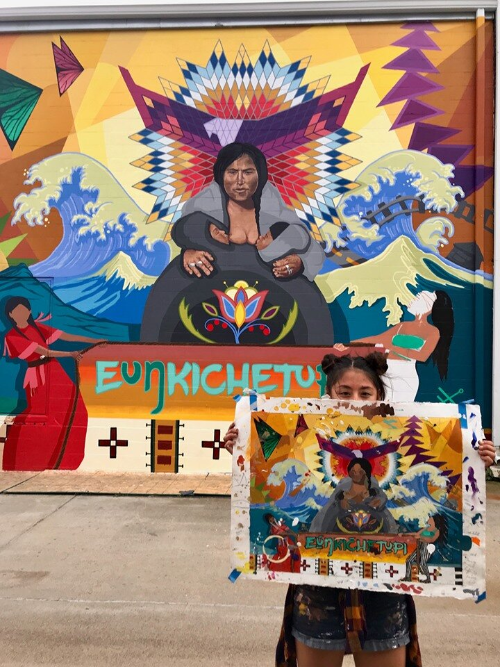 Lead muralist Reyna Hernandez holds up the color study maquette for comparison to the mural.