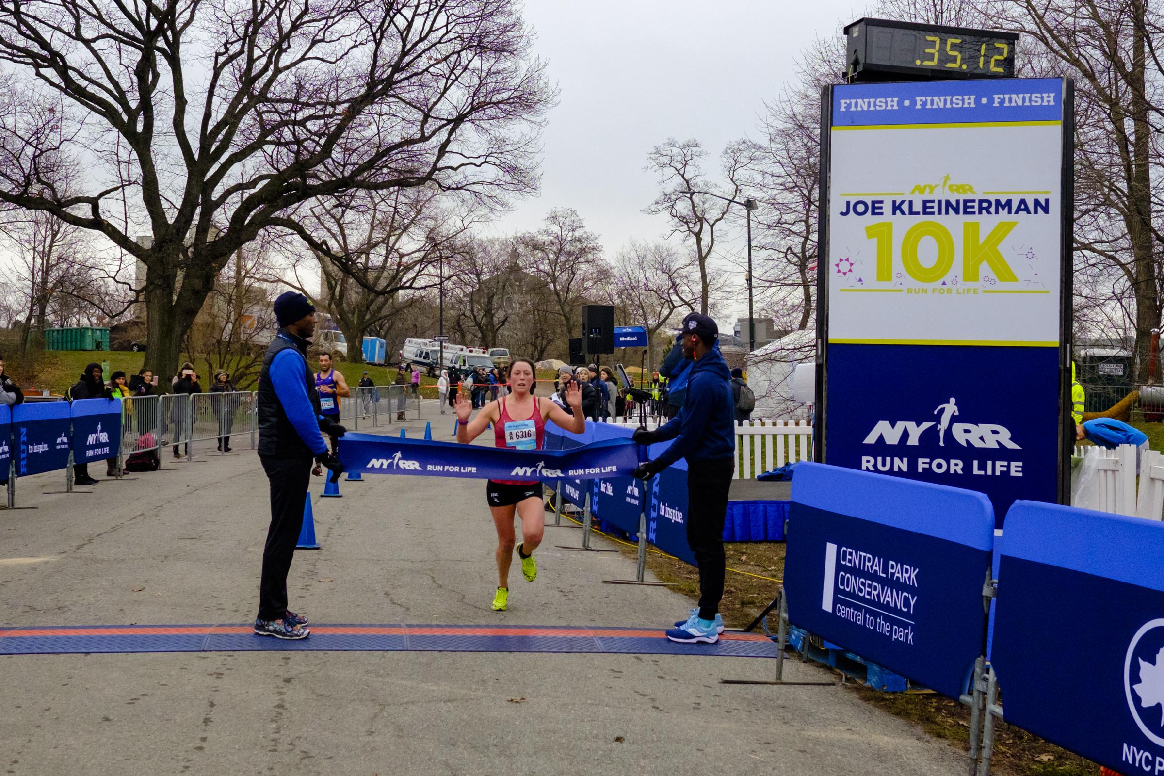 Kieffer breaking the finish-line tape at the 2015 NYRR Joe Kleinerman 10K.