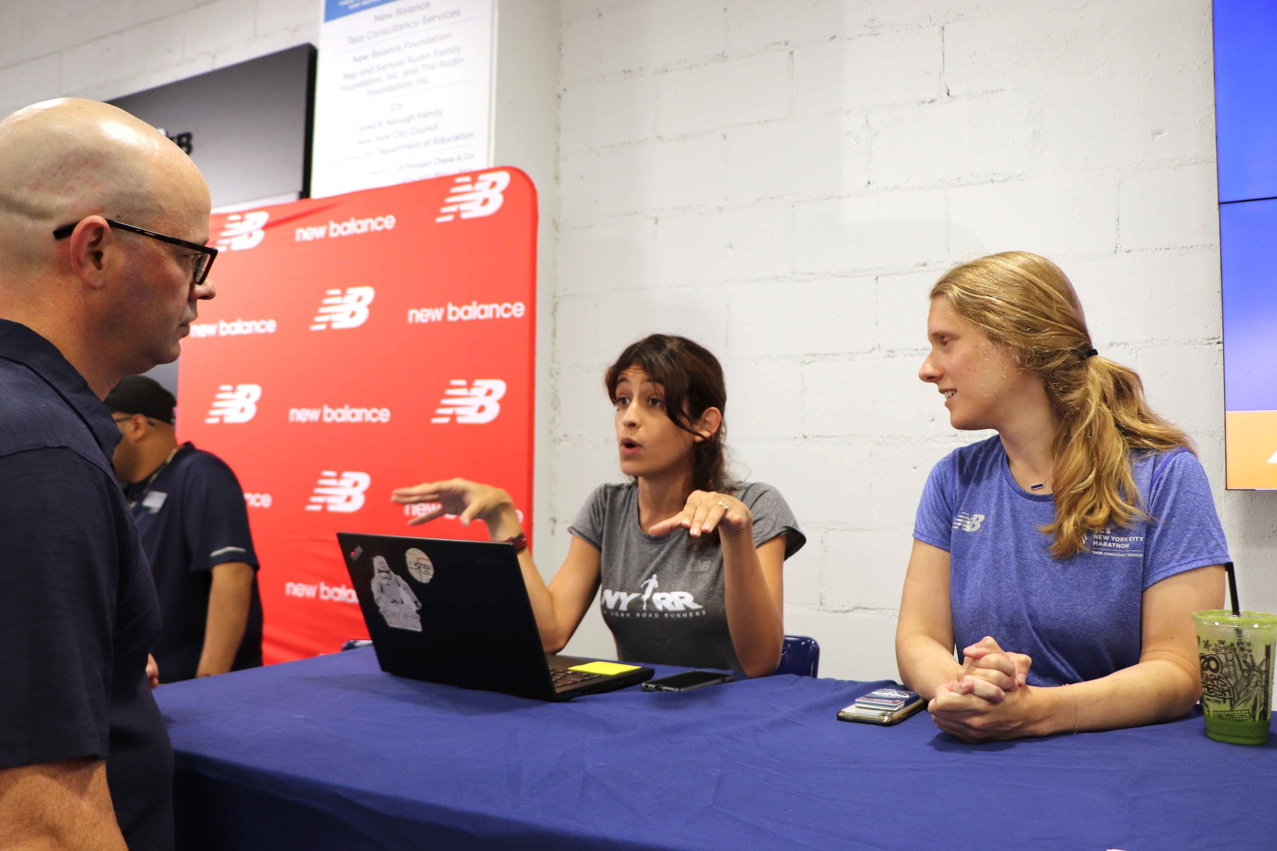 NYRR Virtual Training coach Tammy Salazar, left, at the TCS New York City Marathon Training Expo, discussing the TCS New York City Marathon Virtual Training Program.