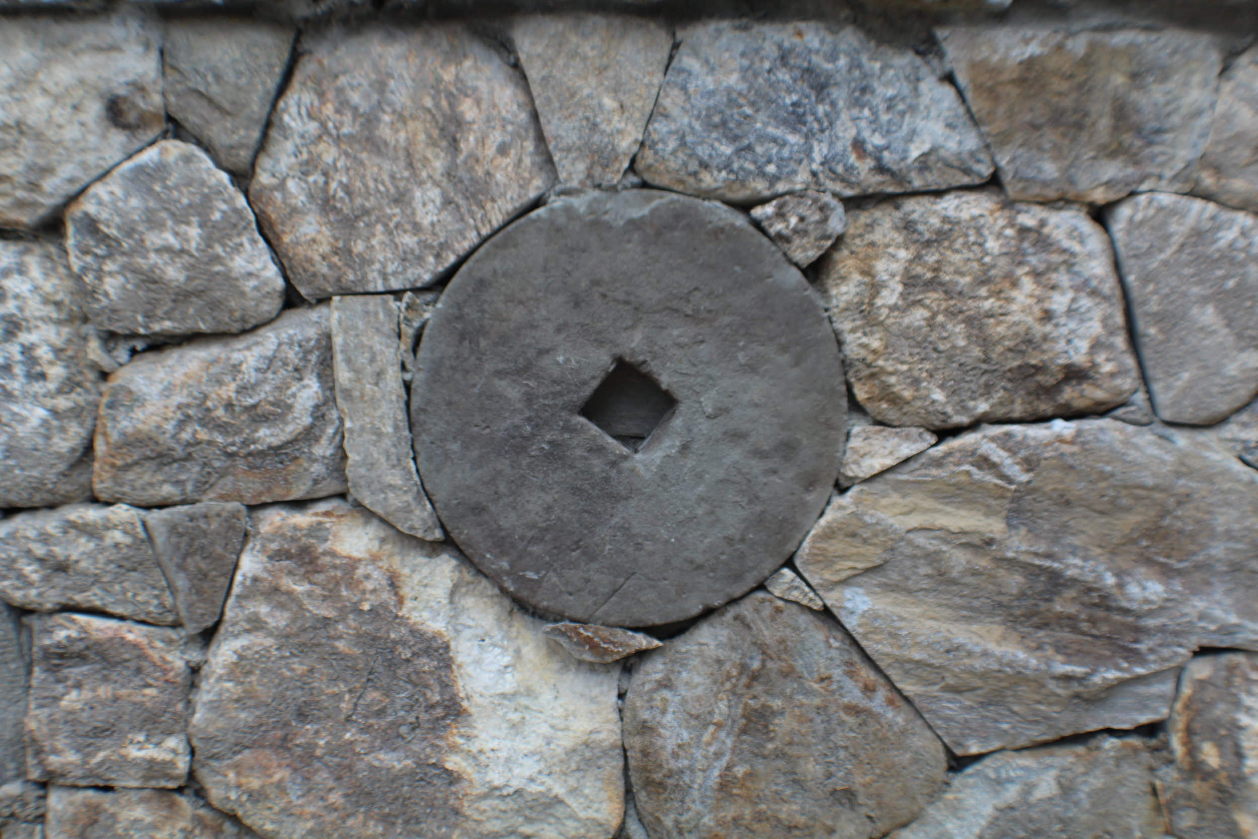 Fieldstone wall with antique grinding wheel