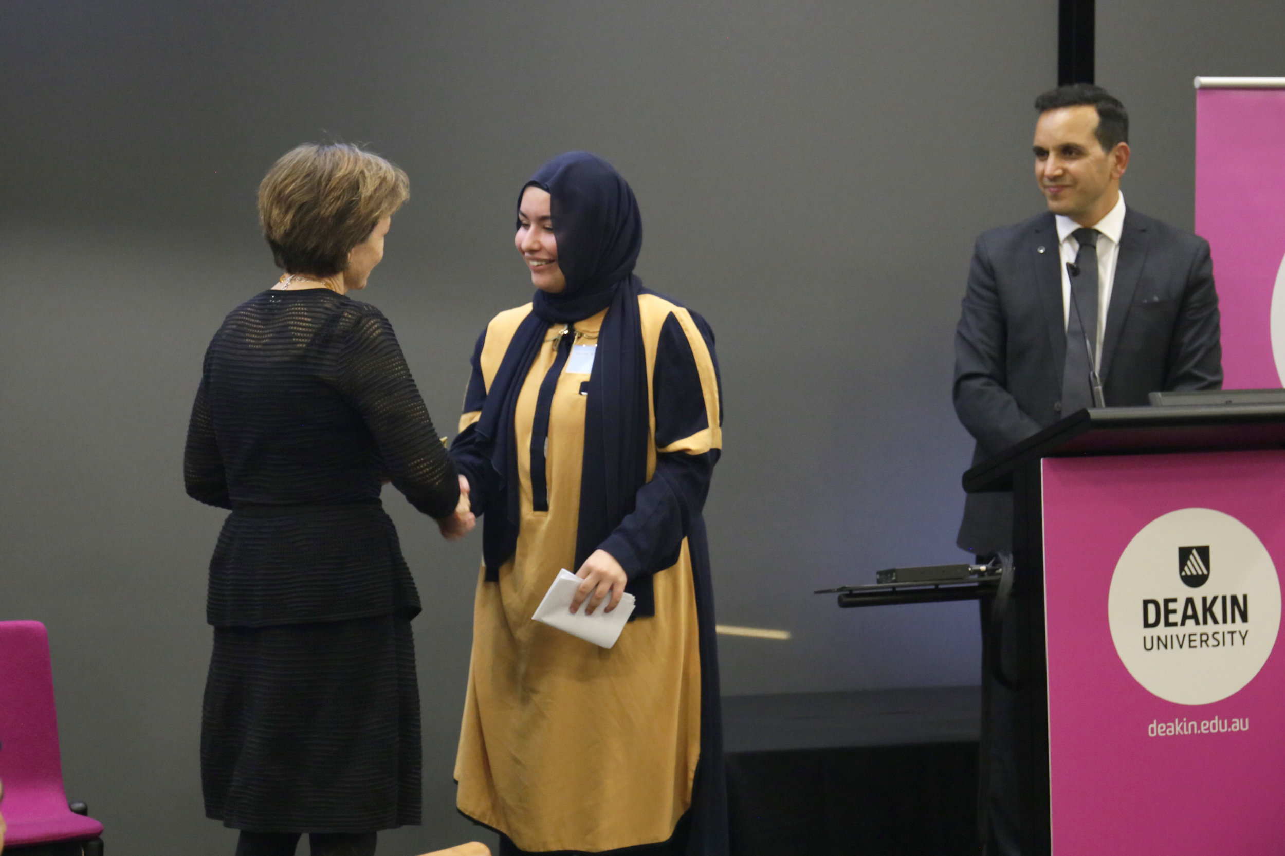 Aleyana Altinors accepting a gift of thanks from Vice-Chancellor Jane den Hollander