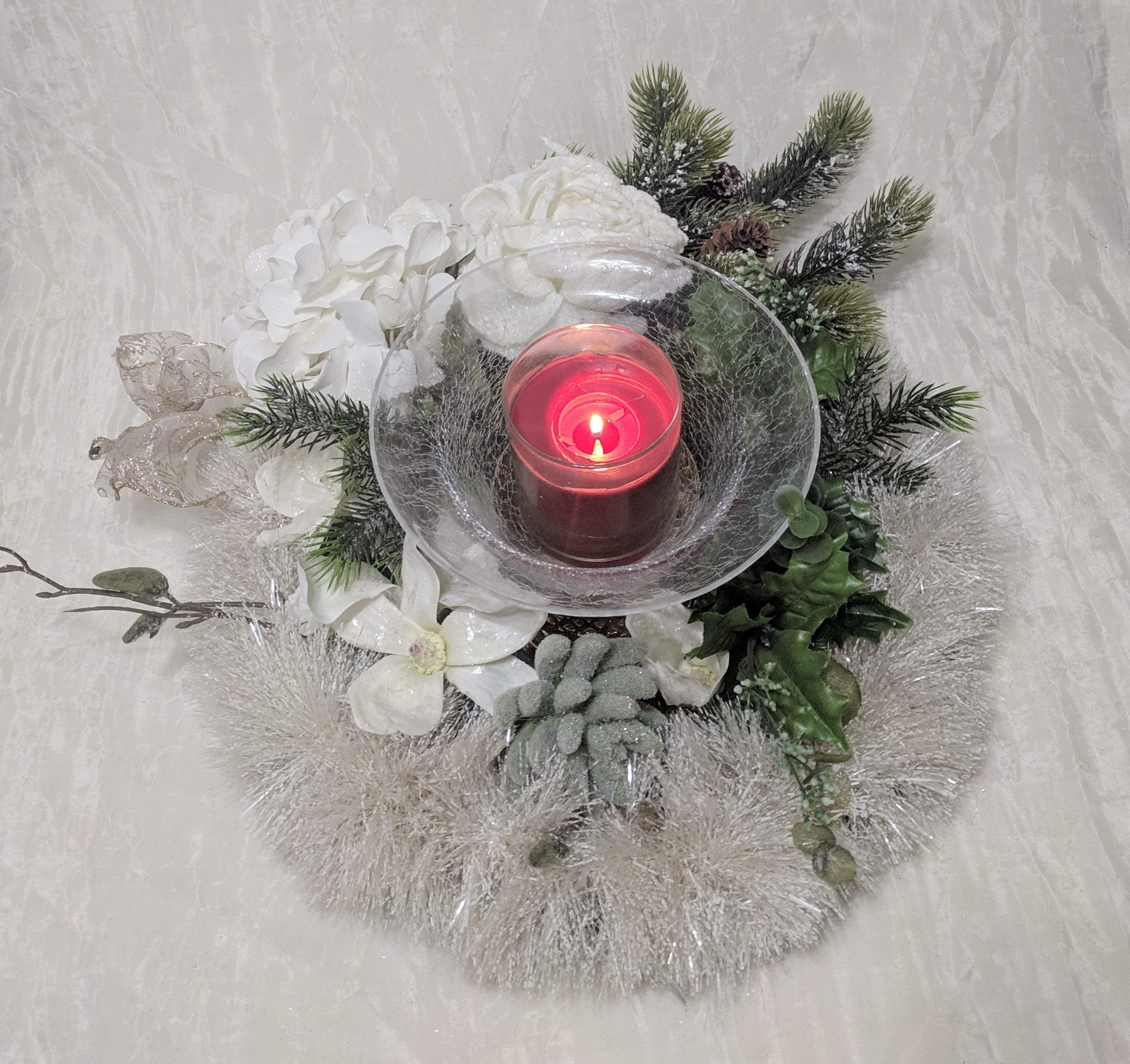 Strike A Festive Glow - Red candle in a jar set in a crackled glass holder, swathed in faux evergreens, pine-cones and silk flowers.