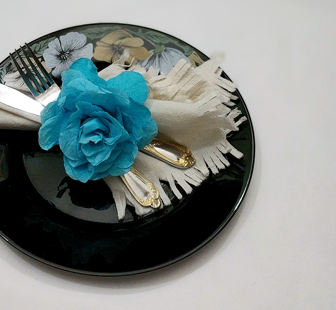 On A Glitter-Free Note - A cotton square fringed at the edges and tied with a blue paper flower, echoes serenity.