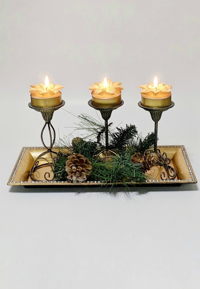 A trio of floral tealights placed on a tray with seasonal trimmings lights up the night.