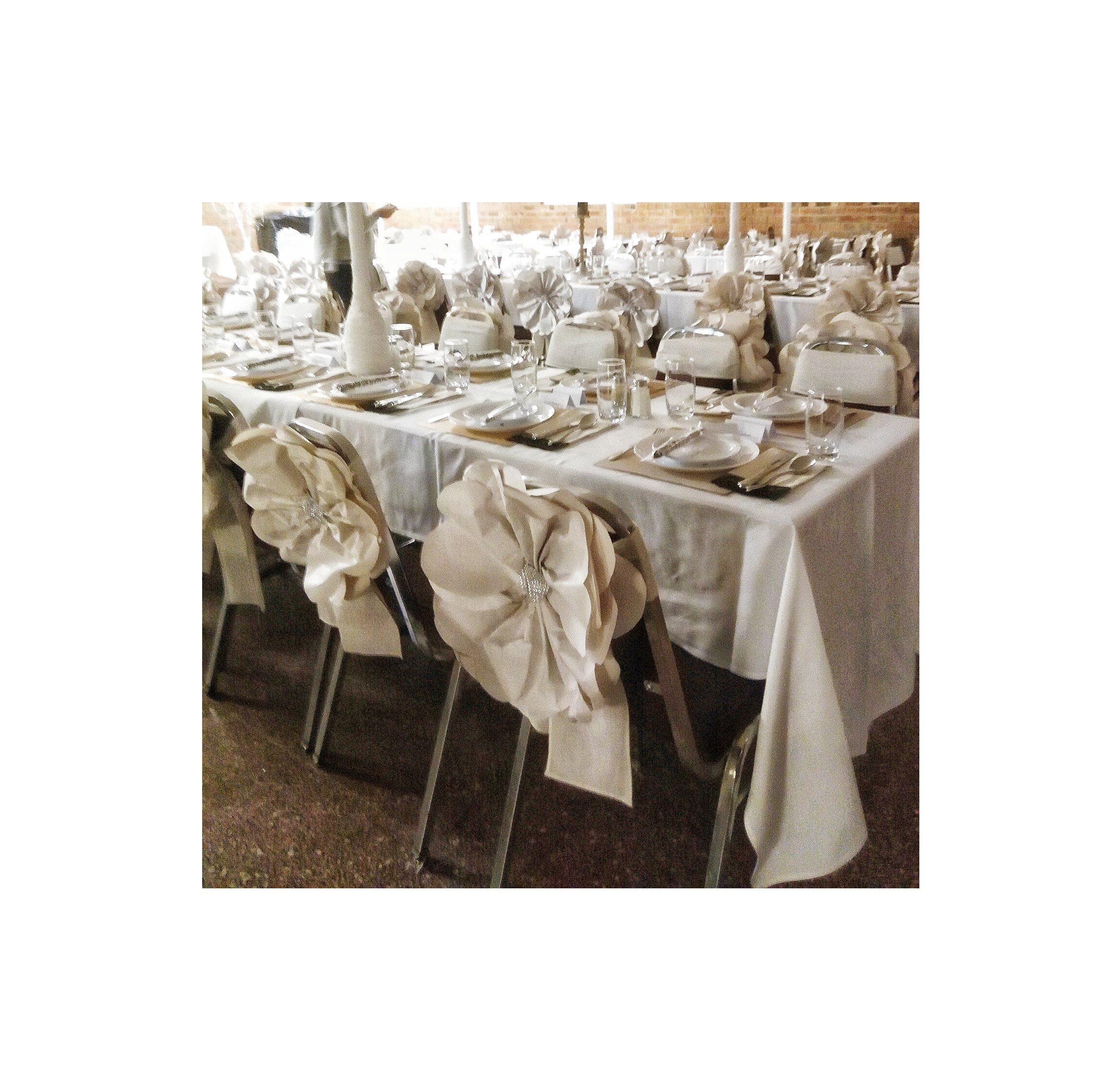Chair Back Decor - Large newsprint flowers and muslin sashes adorn the chairs.