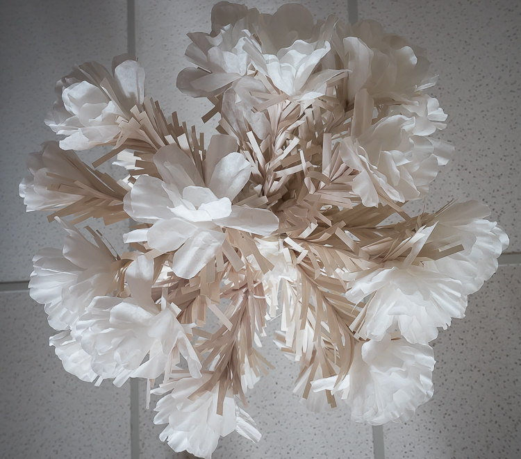 Above:  Coffee filter decoration hung from the ceiling; made with white coffee filters, wooden skewers wrapped in newsprint paper and poked into a styrofoam ball.