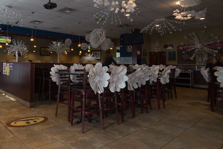Above: Looking towards a restaurant dining room decorated with newsprint paper flowers.